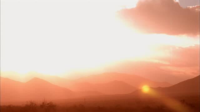 ws, t/l, heavy clouds covering sun above desert, mojave desert, california, usa - viraggio monocromo video stock e b–roll
