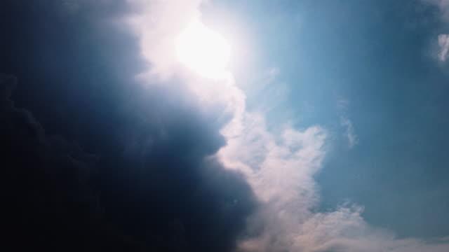 濃い濃い雨嵐雲と太陽の光シャフトが青空を照らす、太陽の光で夕日のタイムラプス。 - light beam点の映像素材/bロール