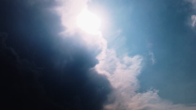 heavy dark rain storm clouds and sun light shafts shining through blue sky, sunset timelapse with sun rays. - cumulonimbus stock videos & royalty-free footage