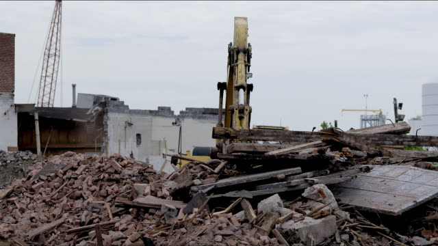 Heavy equipment grappling arm moves and sorts scrap pile debris for recycling in junk yard. - 1