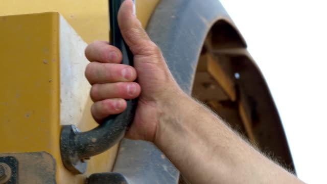 a heavy equipment operator grabs a handle to get in his vehicle - earth mover stock videos & royalty-free footage