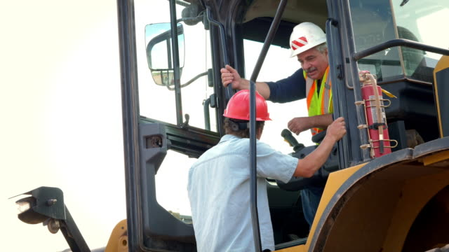 heavy equipment operators have a discussion, older man gives direction to younger worker - machine part stock videos & royalty-free footage