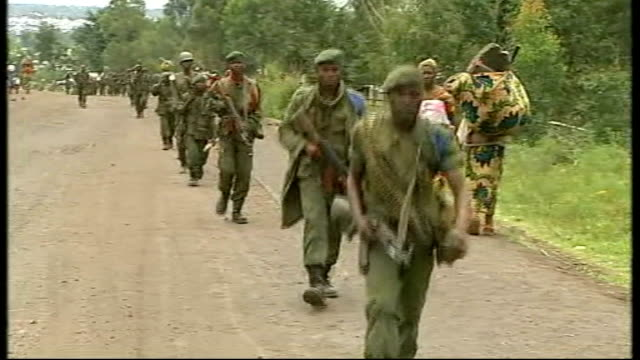 heavy fighting near goma; congolese soldiers march along road, soldier raises gun and points it to camera - camera lowered to ground - democratic republic of the congo stock videos & royalty-free footage