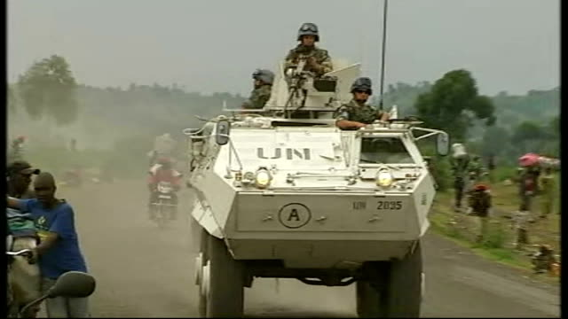 Heavy fighting near Goma UN peacekeeping troops along road in UN armoured vehicles past people carrying belongings
