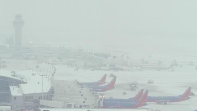 vídeos de stock e filmes b-roll de heavy fog hovering over a snowy airport tarmac. - nevoeiro