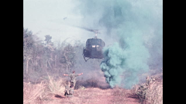 heavy green smoke as soldier holding up arms to guide the helicopter appears crouching soldiers battered by winds camera rocks on the right soldiers... - guerra del vietnam video stock e b–roll