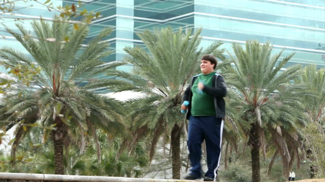 heavy hispanic man power walking with hand weights - racewalking stock videos and b-roll footage