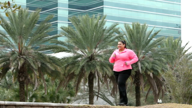 heavy hispanic woman power walking with hand weights - racewalking stock videos and b-roll footage