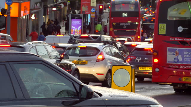 heavy london traffic at rush hour dusk cars passing camera traffic lights jam commuters and pedestrians - road stock videos & royalty-free footage