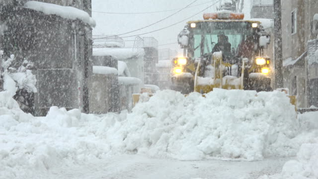 vídeos de stock, filmes e b-roll de heavy machinery clears roads in northern japan during a major winter storm - major road