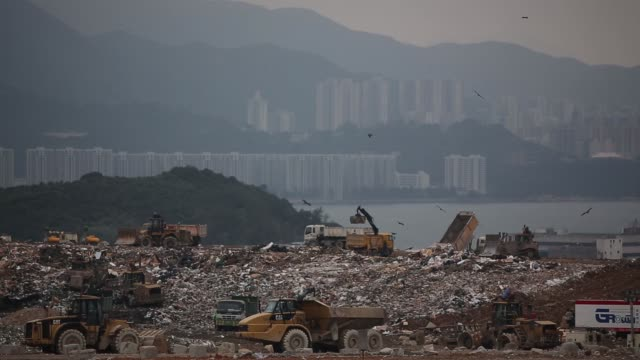 heavy machinery operate on the south east new territories landfill site in the tseung kwan o area as buildings stand in the background in hong kong... - china east asia stock videos & royalty-free footage