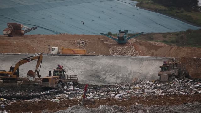 heavy machinery operate on the south east new territories landfill site in the tseung kwan o area in hong kong waste management trucks deliver... - china east asia stock videos & royalty-free footage