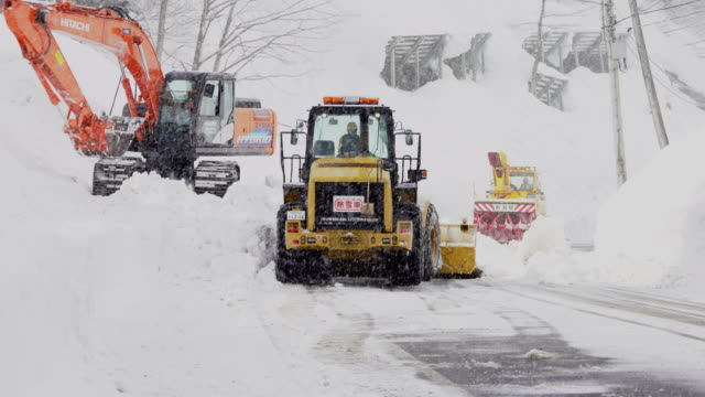 vídeos de stock, filmes e b-roll de heavy machines clear road blocked with snow and ice after major winter storm in japan - major road