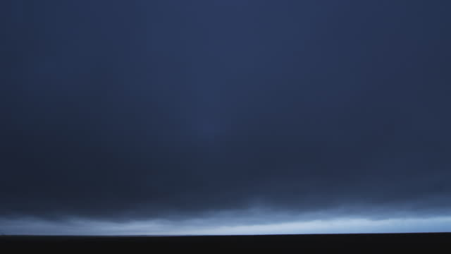 a heavy mass of low dark cloud advances over a prairie horizon at dusk - artbeats 個影片檔及 b 捲影像