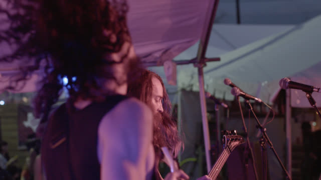 Heavy metal band rock out on music festival stage in slow motion