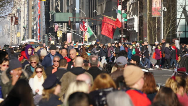heavy midtown manhattan traffic goes through and a crowd of people crosses the fifth avenue during the christmas holidays season at new york city ny usa on dec. 28 2019. - avenue stock videos & royalty-free footage