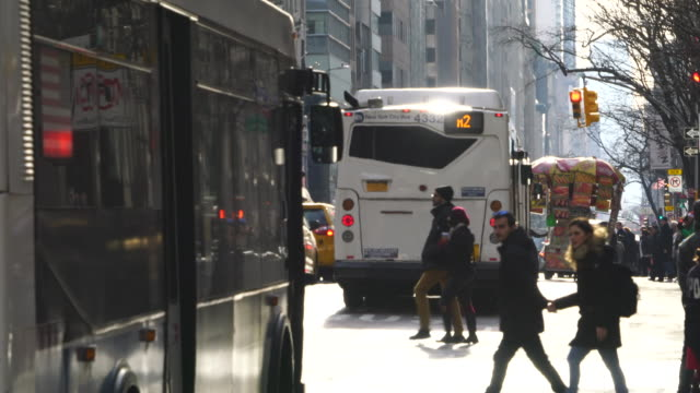 heavy midtown manhattan traffic goes through and people crosses the fifth avenue during the christmas holidays season at new york city ny usa on dec. 25 2019. - yellow taxi stock videos & royalty-free footage