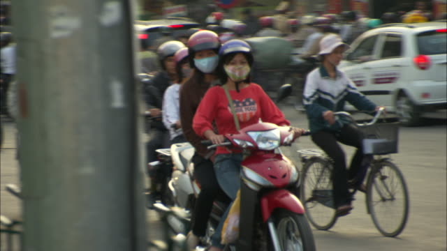heavy moped traffic fills a street in hanoi. - scooter stock videos & royalty-free footage