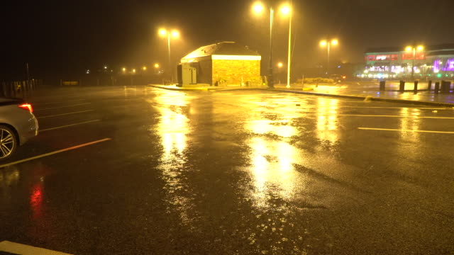Heavy night time windswept rain from a powerful nor'easter is illuminated by street lights at a marina on Long Island