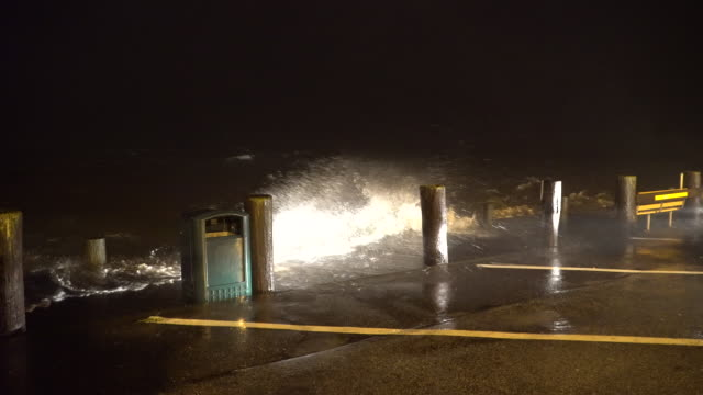 Heavy rain and very rough surf crash over a dock at a marina on Long Island during an intense night time nor'easter