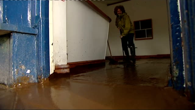 heavy rain and wind to continue across uk / motorist killed; wales: llanberis: int mud swept from floor of shop following flooding ext man emptying... - sidewalk gutter stock videos & royalty-free footage