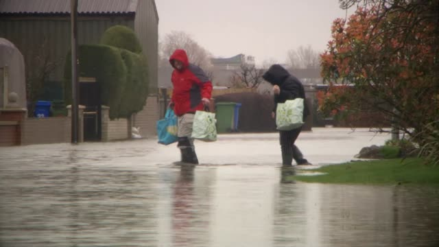 heavy rain brings further flooding ahead of arrival of storm jorge england yorkshire east cowick ext floodwater surrounding house where the residents... - walking in water stock videos & royalty-free footage