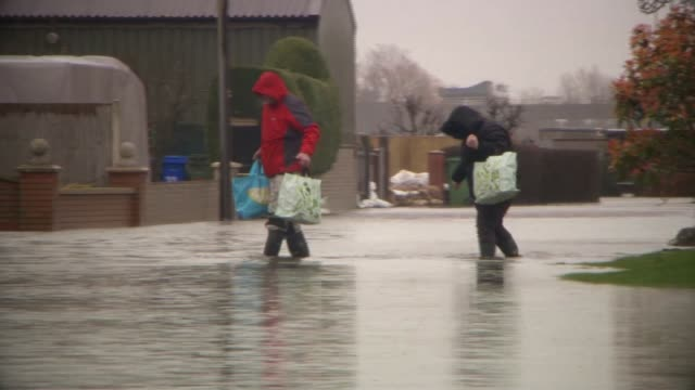 heavy rain brings further flooding ahead of arrival of storm jorge england yorkshire east cowick ext people carrying shopping as wading along flooded... - walking in water stock videos & royalty-free footage