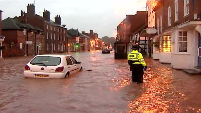 worcestershire tenbury wells ext car partly submerged in flood water flooded area of main street police officer standing in flooded street / fast... - tenbury wells stock videos and b-roll footage