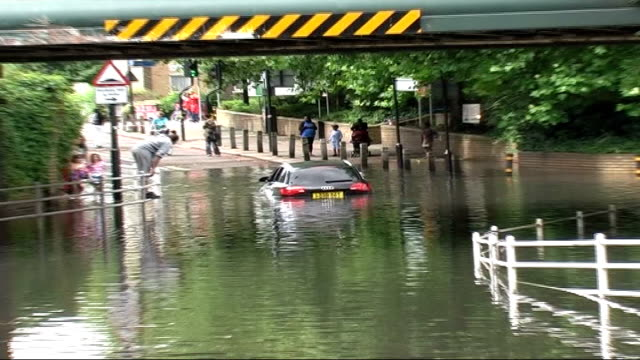 car stranded in floodwater in flooded underpass under bridge car along road throign up spray as heavy rain falls traffic along motorway through heavy... - underpass stock videos and b-roll footage