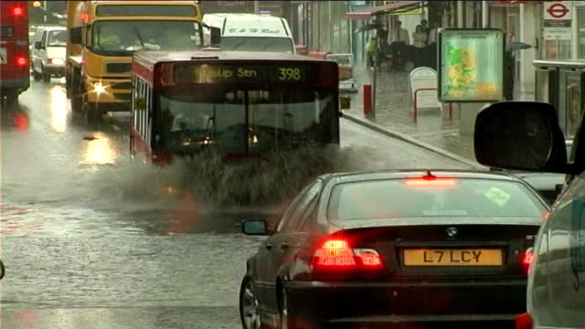 ext car along road through heavy rain rain running along gutter bus driving through flooded underpass man with child in carry backpack along through... - 2007 stock-videos und b-roll-filmmaterial