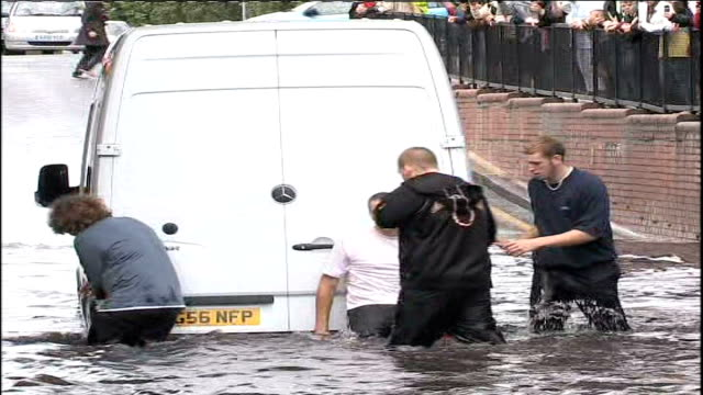 heavy rain causes more flooding worcester park men pushing car from floodwater men pushing van from floodwater women walking along through floodwater... - 2007 stock-videos und b-roll-filmmaterial