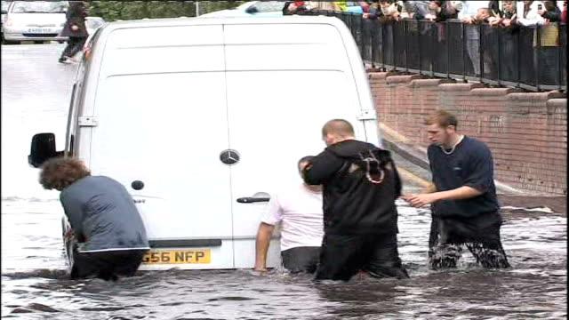 heavy rain causes more flooding; worcester park: men pushing car from floodwater men pushing van from floodwater women walking along through... - pushing stock videos & royalty-free footage