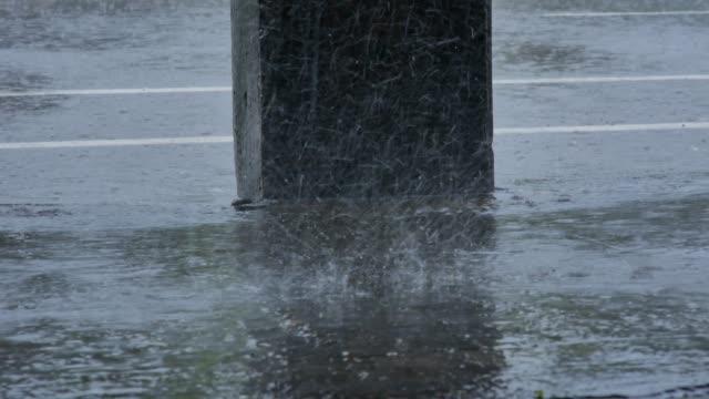 starkregen fällt bei regen auf die stadtstraße. regenwetter - schwer stock-videos und b-roll-filmmaterial
