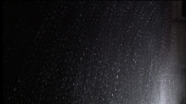 heavy rain falls against a black background. - meteorologie stock-videos und b-roll-filmmaterial