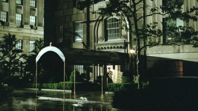 vidéos et rushes de heavy rain falls on an upscale hotel as lightning flashes and traffic passes. - palace