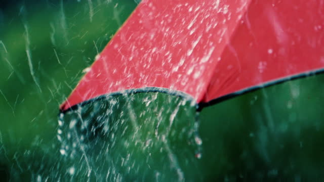 Starker Regen fällt auf roten Regenschirm