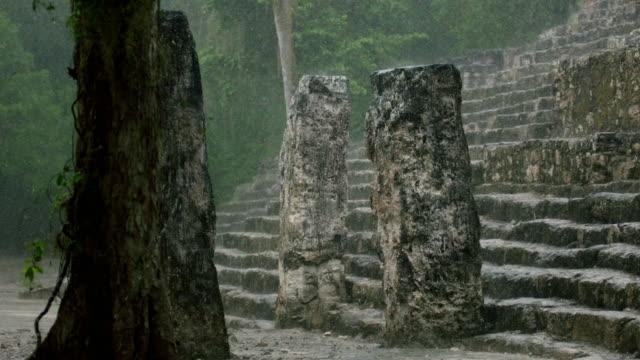 heavy rain falls onto pillars on a mayan site - old ruin stock videos & royalty-free footage