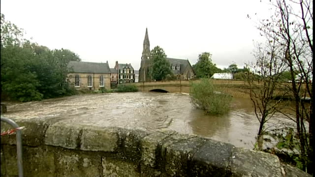 heavy rain leads to flooding in northern england; england: northumberland: morpeth: ext 'flood' and 'road closed' signs to swollen river 'morpeth'... - northumberland video stock e b–roll