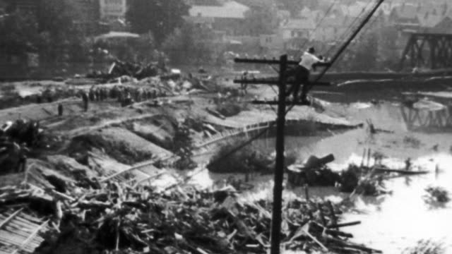 vidéos et rushes de / heavy rain pours on flooddevastated house and landscape / high flood waters pass just under fallen utility lines / a collapsed home / bridges and... - 1955