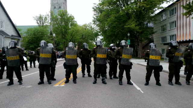 heavy riot police presence on g7 protest route in quebec city. - 緊急用具点の映像素材/bロール