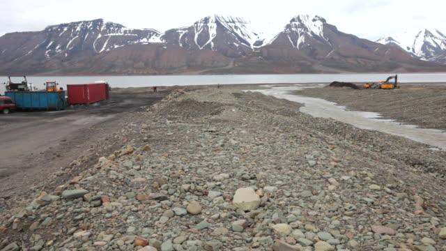 Heavy road construction machines on a stony beach at Adventfjorden near Longyearbyen, Svalbard archipelago