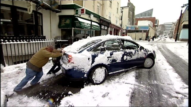 heavy snow across britain causes chaos; two men pushing car out of snowdrift at side of road car slowly manoeuvring on icy road snow gritting lorry... - pushing stock videos & royalty-free footage