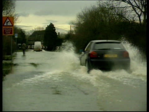 Heavy snow and flooding ITN Cleveland Rough waves breaking on rocky shoreline Cambridgeshire BV Car away thru heavily flooded road CMS Water level...