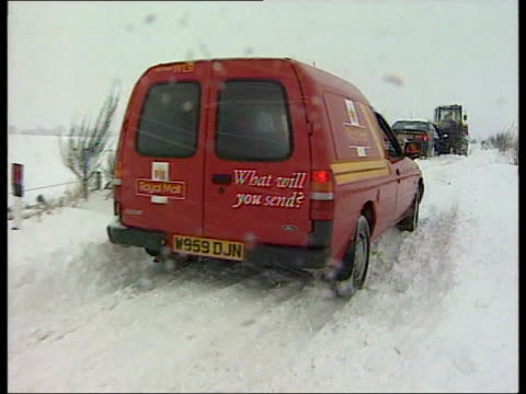Heavy snow and flooding ITN Cars along snowy road TLMS Ditto DAY Men with shovels clearing road Snowplough along PULL OUT 'Road Closed' sign...