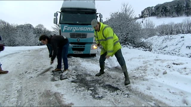 road and rail disruption devon workmen shovelling snow slush and ice from a38 road where hgv lorry has got stuck workmen using spades to clear... - slush stock videos and b-roll footage