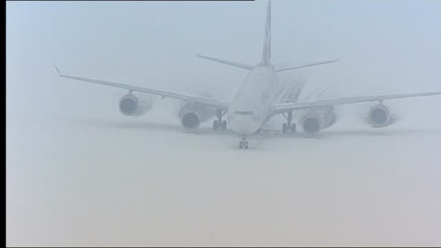 heavy snow and ice forces airports to close aerials of heathrow airport england london heathrow airport views / aerials of heathrow airport covered... - taxiway stock-videos und b-roll-filmmaterial