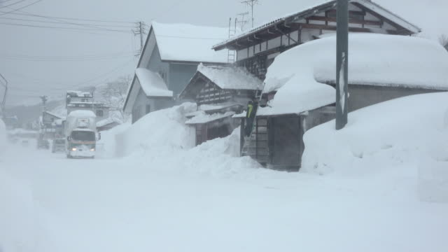 heavy snow and strong winds hit rural town in japan - 深い雪点の映像素材/bロール