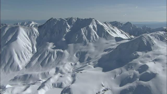 Heavy snow blankets the rugged Kita Alps in the Tateyama Mountain Range, Japan.