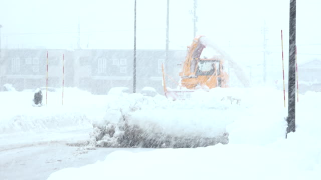 heavy snow clearing machinery clears road during major winter storm in northern japan - 深い雪点の映像素材/bロール