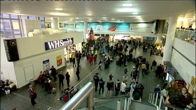 Heavy snow continues to cause travel chaos Gatwick Airport People queueing at hotel reservations counter / International Arrivals information screens...